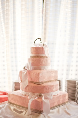 Pink wedding cake sitting in a reception hall.