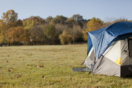 A tent sits outside while camping in the autumn season.