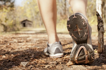 Shoes of a woman walking on a trail in the woods int the fall.