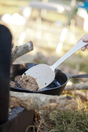 Cooking sausage in a cast iron skillet over an open campfire.  photo