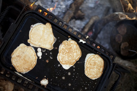 flapjacks: Browned pancakes on a skillet over an open campfire.