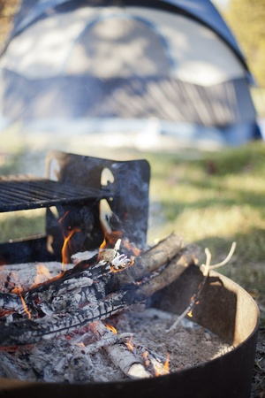 A burning campfire with a tent in the background.