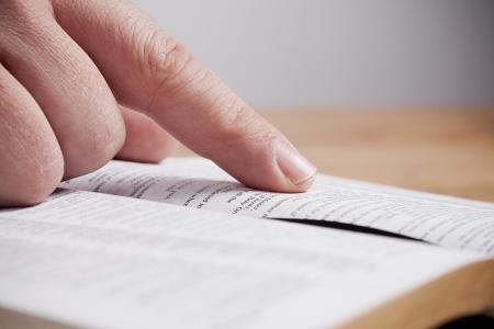 pastor: Close up of man reading through the Bible. Stock Photo
