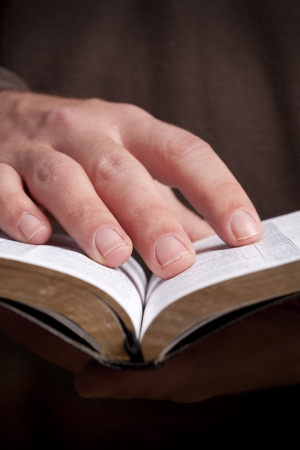 holding bible: Man holding open Bible in his hands.