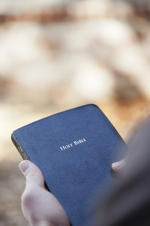 Man holding a Bible outside with shallow depth of field.