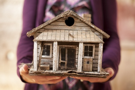 minature: Woman holding old minature house that is falling apart.  Stock Photo