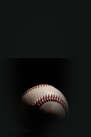 Baseball isolated on black background with dramatic lighting  Vertical orientation
