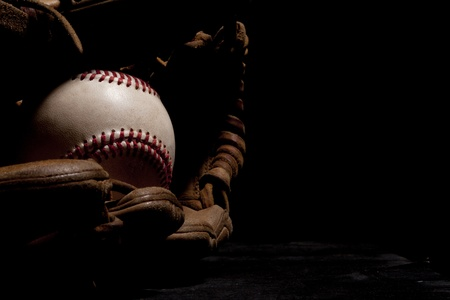 Dramatic lighting of an old baseball and glove isolated on black background   photo