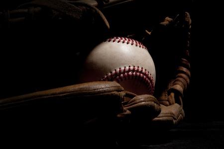 guante de beisbol: Macro foto de béisbol y un guante desgastado aislado en un fondo negro