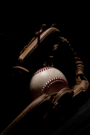 Vertical shot of an old baseball and glove isolated on black background   Imagens