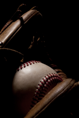 Macro shot of worn baseball glove and ball with dramatic lighting on black background  photo