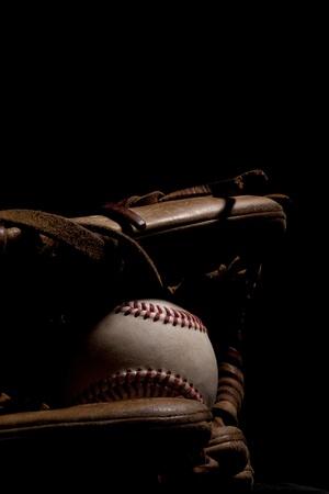 guante de beisbol: Desgaste del b�isbol y un guante aislado en iluminaci�n de fondo negro dram�tico