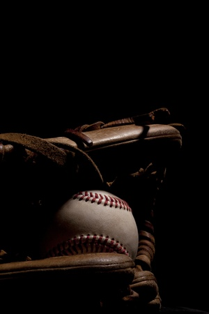 Worn baseball and glove isolated on black background  Dramatic lighting