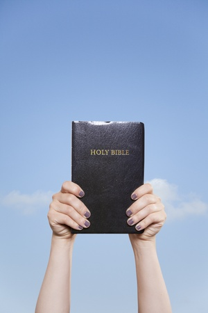 A woman holds a Bible high with in the sky two hands