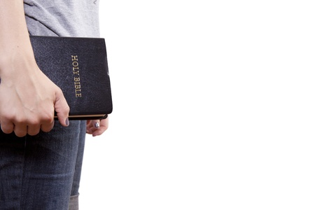 A woman stands and holds a Bible at her side  Isolated on white