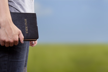 A woman stands and holds a Bible at her side in an open field   photo