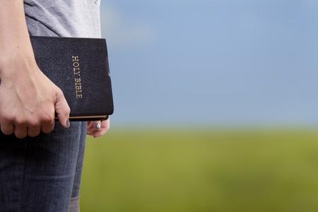biblia: Una mujer se levanta y sostiene una Biblia a su lado en un campo abierto Foto de archivo