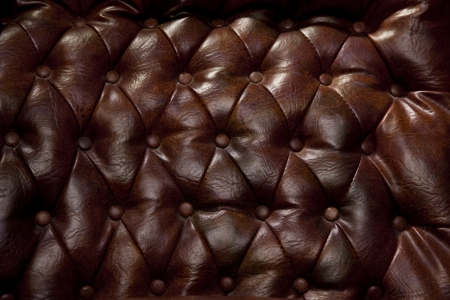Close-up of vintage leather couch with seams and buttons.