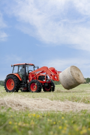 Tractor hauling a round bale an open field with blue sky.