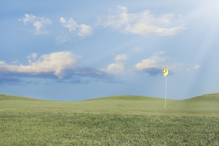 Golf hole with yellow flag, ball, and beautiful blue sky.  photo