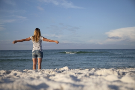 A woman feels the breeze from the ocean while standing on the sand  Stock Photo - 14689093