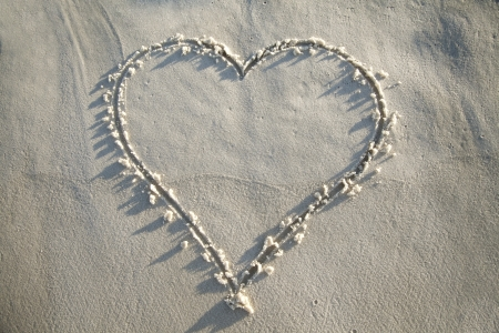 A heart is drawn in the white sand with the morning sun shining on it photo