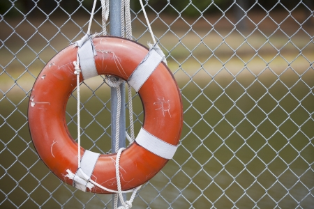 wire fence: A rugged orange life ring hangs on a chain link fence outside in the summer  Stock Photo