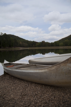 Two silver canoes sit in the gravel bed by a lake with the reflection of a blue sky Stock Photo - 14782022