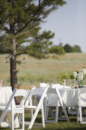 White tables and chairs are set up in a country field with colorful flowers on them. photo