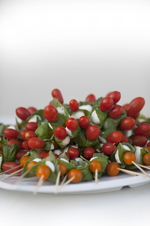 A plate is piled full of freshly made tomato, mozzarella, and basil skewers. photo
