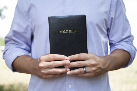 A man stands outside and holds a  black bible with both hands.