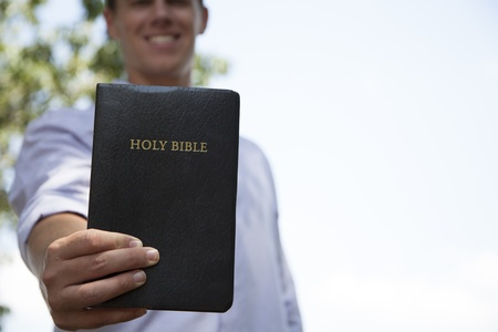 holding close: A young man stands outside while holding out a bible in front of him.