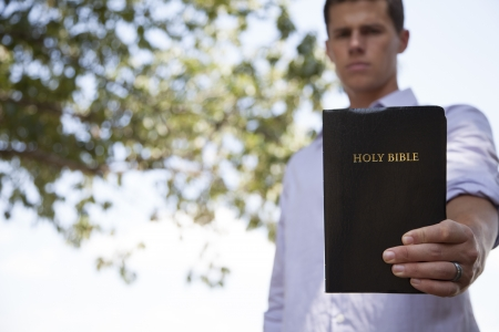 A young, confident man stands outside holding a black bible with one hand. photo