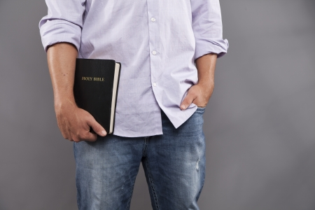 casually: A man stands indoors with one hand holding a black bible and the other hand casually in his jeans pocket.