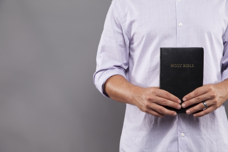 A man stands indoors holding a black bible in front of him with both hands Imagens