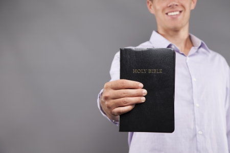 A young man dressed in a casual dress shirt is standing indoors holding a black bible out in front of him while smiling. photo