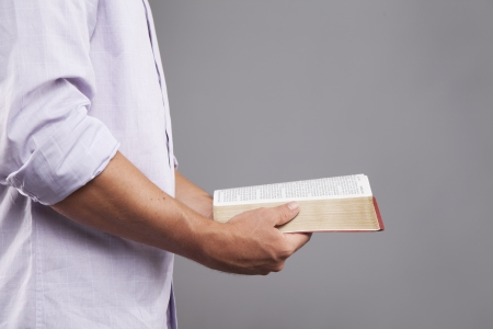 A man stands indoors holding a bible out in front of him with both hands. photo