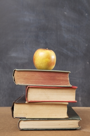 A stack of old books with an apple on top sit on a desk in front of a blackboard  photo