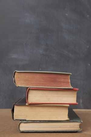 Four old school books are stacked unevenly on a desk in front of a blackboard  Stock fotó