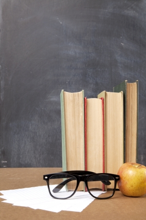 Books, paper, glasses, and an apple sit on a school desk with a blackboard in the background  photo