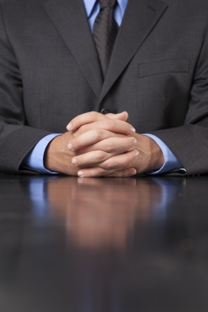 A businessman dressed in a suit sits at a desk with his hands clasped showing power and confidence  photo
