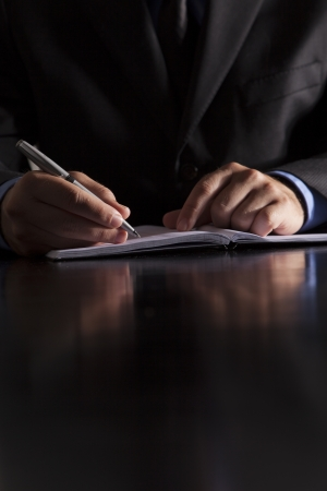 A businessman dressed in a suit sits at a desk and writes in a notebook