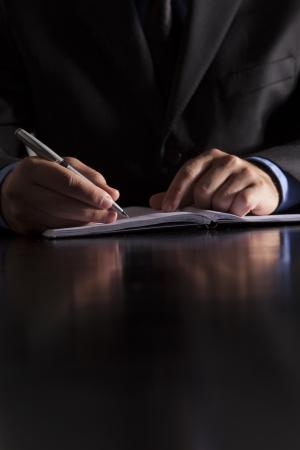 document management: Un hombre de negocios vestido con un traje sentado en un escritorio y escribe en un cuaderno