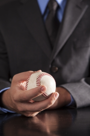 A young executive sits at his desk holding a baseball  photo