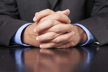 A business man dressed in a suit sits at a desk and clasps his hands firmly