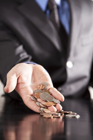 accountancy: An executive holds an overflowing amount of change in his outstretched hand  Stock Photo
