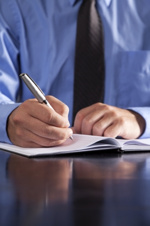 A young businessman writes in a notebook while sitting at a desk. photo