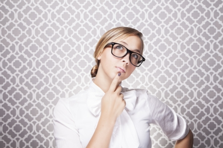 A young teacher or student wearing glasses is in in deep thought while standing in front of a modern pattern. Stock Photo - 15218037