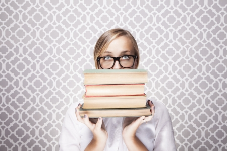 A young woman wearing glasses peers over a tall stack of books.