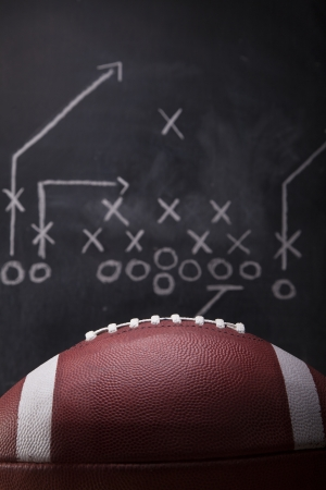 An American football and a hand drawn chalkboard play